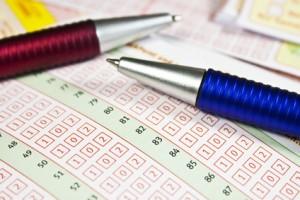 Zwei Kugelschreibe liegen auf Lottoscheinen