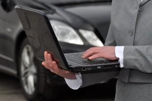 Jemand tippt auf einem Laptop, dahinter ein Auto für Logistik