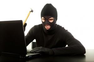 Ein Dieb mit einem Hammer vor einem Laptop