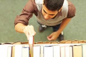 Student nimmt ein Buch aus einem Regal